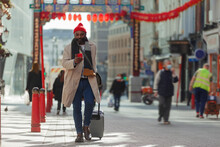 Male Tourist With Suitcase And Smart Phone At Chinatown Gate, London