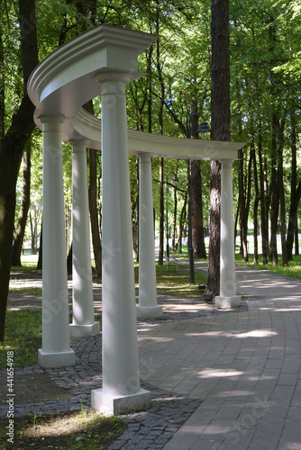 Billede på lærred From the snow-white colonnade in the park, walking paths diverge in different directions like rays