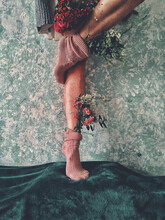 Vertical Shot Of A Female With Flowers Standing On A Dark Green Fabric