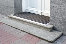 Stone Threshold With Foot Mat At The Entrance Door Made Of White Wood And Gray Stone Facade Cladding Of Retro European Architecture Building Closeup Side View; Nobody.