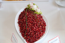 Pomegranate Seeds On A White Plate With Decorative Flowers
