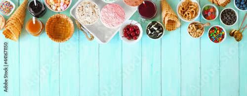 Summer ice cream buffet with assorted of flavors and sweet toppings. Above view table scene on a blue wood background.