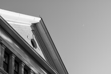 Black And White Of Peaked Gabled Roof With Oculus Window On Exterior Facade. Sliver Moon In Sky. Room For Text.