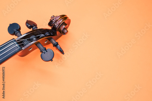 Fotografie, Obraz Pegbox of a violin on orange background with a copy space