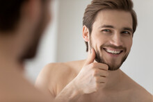 Happy Millennial Young Handsome Man Looking In Mirror In Bathroom With Toothy Smile, Scanning Facial Skin And Stylish Stubble. Guy Satisfied With Male Beauty Care Product. Skincare, Home Spa Concept