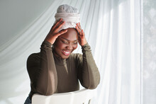 Happy African Woman Sitting On Chair With Hands On Head