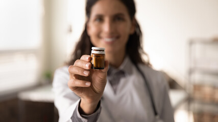 Crop close up blurred background of female doctor hold bottle medication prescribe pills to sick patient. Woman GP or therapist recommend good quality medicines. Healthcare, treatment concept.