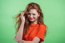 Young Woman With Red Hairstyle Looking To Camera, Flirting. Beautiful Model Girl On Green Studio Background.
