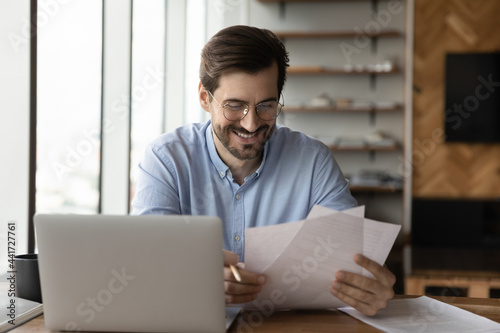 Fotografia Happy young successful businessman manager employee entrepreneur analyzing financial paper documents, feeling satisfied with sales data statistics results, working alone on project in modern office