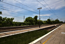 Railroad Tracks Seen From A Platform  Of A Empty Station In The Italian Countryside At Midday In Summer