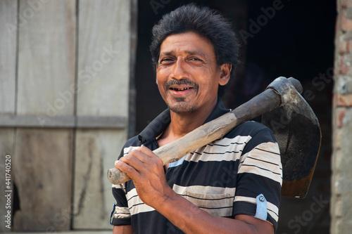 Fotografie, Obraz Portrait of a Farmer holding a spade on her shoulder