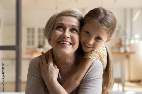 Obraz na plátně Joyful small 7s kid girl cuddling from back laughing old middle aged grandmother, enjoying tender sweet moment together at home