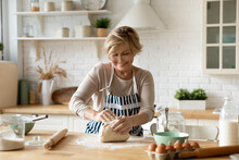 Happy Beautiful Older Middle Aged Retired Woman In Eyeglasses Wearing Apron Kneading Dough, Involved In Preparing Homemade Pastry Alone In Modern Kitchen, Domestic Culinary Cooking Activity Concept.
