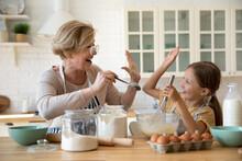 Happy Beautiful Older Senior Grandmother Giving High Five To Joyful Adorable Preschool Kid Granddaughter, Feeling Proud Preparing Homemade Pastry Or Pancakes Together In Modern Kitchen On Weekend.