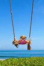 Happy Girl Have Fun Swinging High In Mid Air. Flying Up Upside Down On Rope Swing On Sea Beach. Travel Adventure On Paradise Tropical Island. Family Lifestyle, Activity On Summer Vacation With Kids
