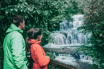 New Zealand tourists at waterfall nature landscape. People looking at Purakaunui Falls, a famous waterfall in the Purakaunui River in the Catlins of the southern South Island of New Zealand