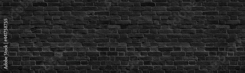Foto Old black shabby brick wall wide panoramic texture
