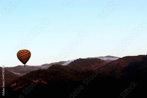 Obraz na plátně Hot Air Balloon Flying Over Mountains Against Clear Sky