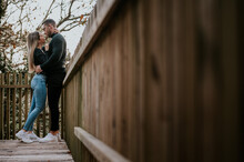 Couple Embracing While Standing Near Wooden Fence