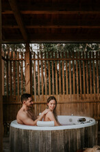 Naked Couple Relaxing In Jacuzzi In Wooden Cabin