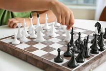 Cute African-American Boy Playing Chess At Home, Closeup
