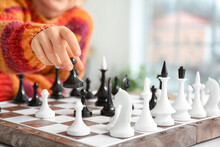 Cute Little Girl Playing Chess At Home, Closeup