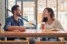 Laughing Ethnic Couple Speaking At Restaurant Table With Beverages