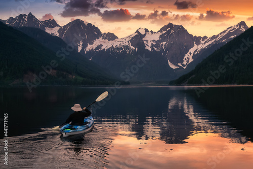 Murais de parede Adventurous man kayaking in the water surrounded by the Beautiful Canadian Mountain Landscape
