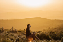 Serene Woman Sitting On Hill In Mountains At Sunset
