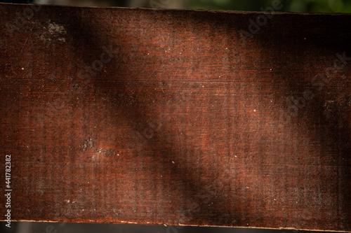 Ciemno brązowe drewniane tło, tekstura desek z pęknięciami.