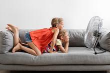 Smiling Young Girls On Sofa Facing A Fan