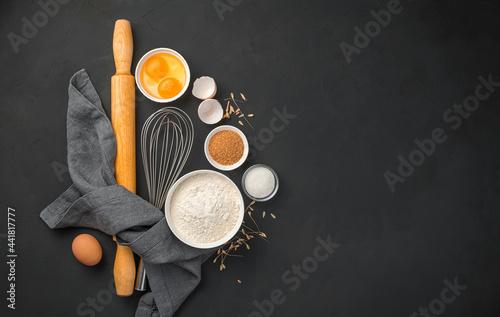 Murais de parede Flour, eggs, sugar and rolling pin on a black background