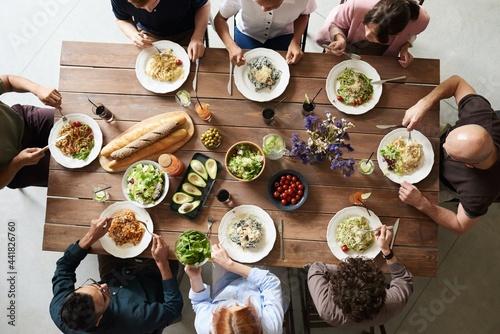 Group of people sitting at beautiful dinner table enjoying different Italian dis Fototapet