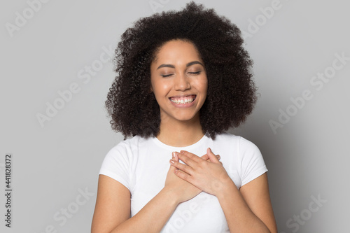 Foto Smiling millennial African American woman isolated on grey studio background keep hands at chest feel grateful