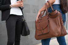 The Hands And Handbags Of Two Business Women