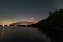 A View Of The Night Sky Over Derwent Water In The English Lake District With The Orange Glow Of Keswick