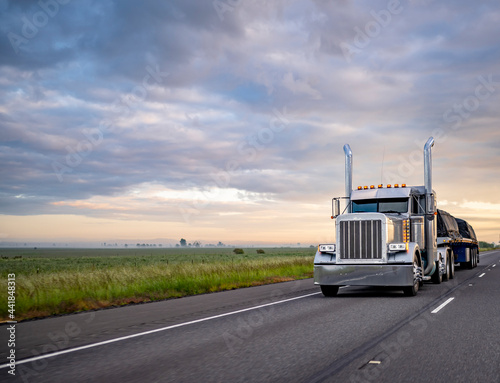 Fotografie, Obraz Classic American idol big rig semi truck with turned on light and high exhaust p