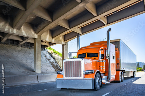 Fotografia Stylish orange classic big rig semi truck with chrome accessories and exhaust pi