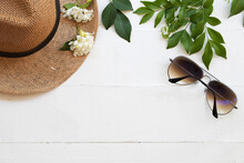 Sunglasses ,hat And Flowers Of Lifestyle Woman Relax Arrangement Flay Lay Style On Background  Wooden White