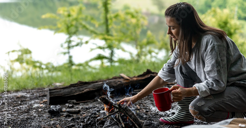 Obraz na plátně Girl with a cup of hot drink near the fire in nature.