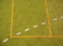 Border Lines On Court. Worn Out Green Red Hairy Carpet On Outside Hanball Playground. Tartan Track.