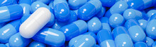 Close Up Of White Pill Capsule In Many Blue Pills Capsules. Medicine And Specialty Pharmaceuticals.