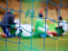 Footballists And Stadium Arena Soccer Field Defocused. Vew Through Soccer Gate Net.
