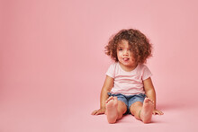 Charming Kid With Tongue Out On Pink Background