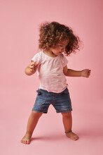 Cute Toddler Girl In Casual Wear Dancing On Pink Background