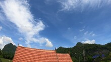 White Clouds Blue Sky Over Rooftop With Cows Grassing On Green Field