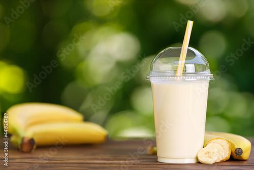 Obraz na plátně banana milkshake in disposable plastic glass on wooden table