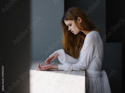 Fotografia, Obraz red-haired Woman in a white dress enriched herself on the windowsill near the wi