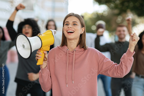 Cuadros en Lienzo Enthusiastic blonde lady activist with megaphone on the street