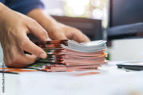 Tela Pile of presentation brochure document concept : Businessman hands working in bu